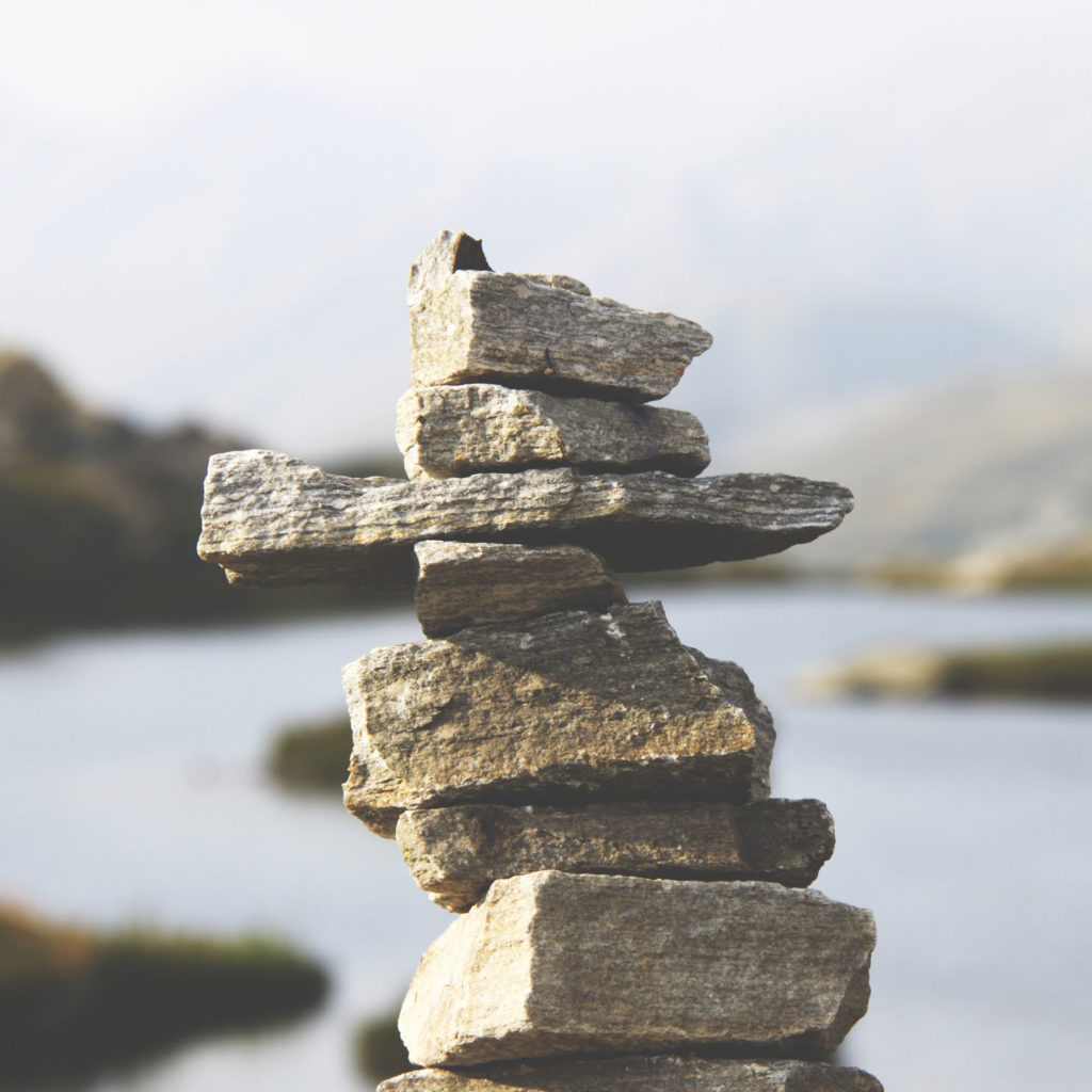 photo of rocks stacked in nature near a body of water