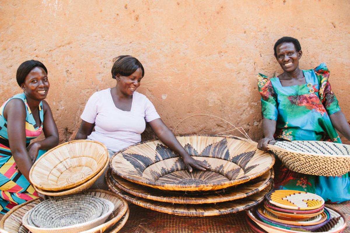 African artisans sit among piles of woven baskets
