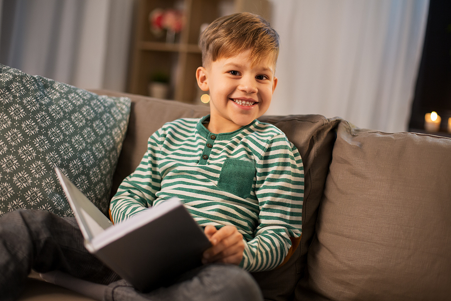 A happy child reading a book on the couch