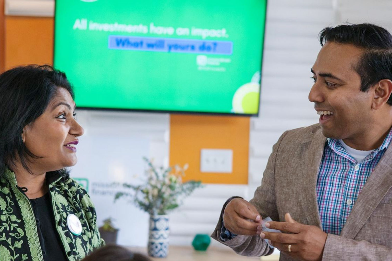 two professionals discuss impact investing at a meeting