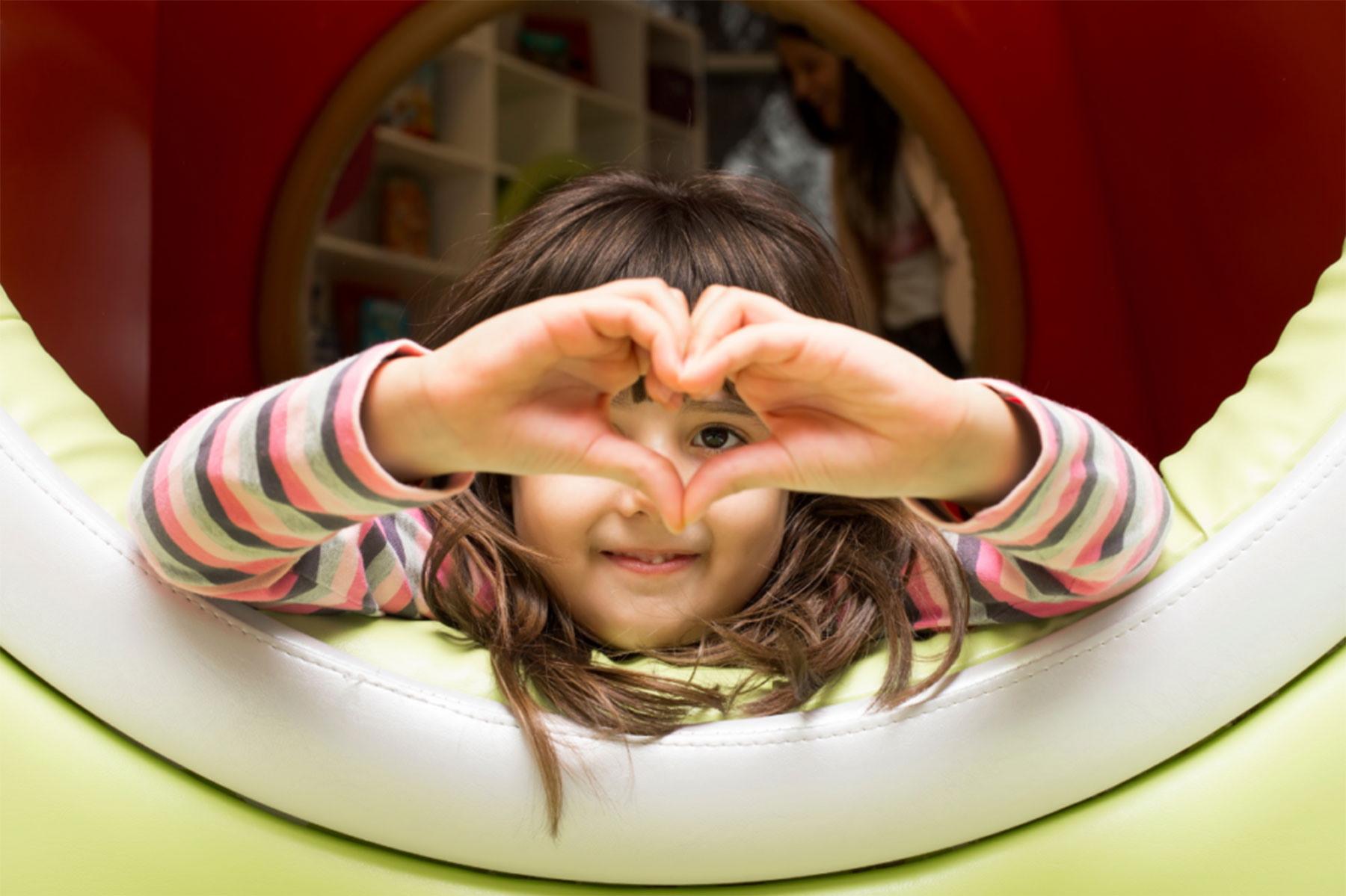 a child makes a heart with her hands