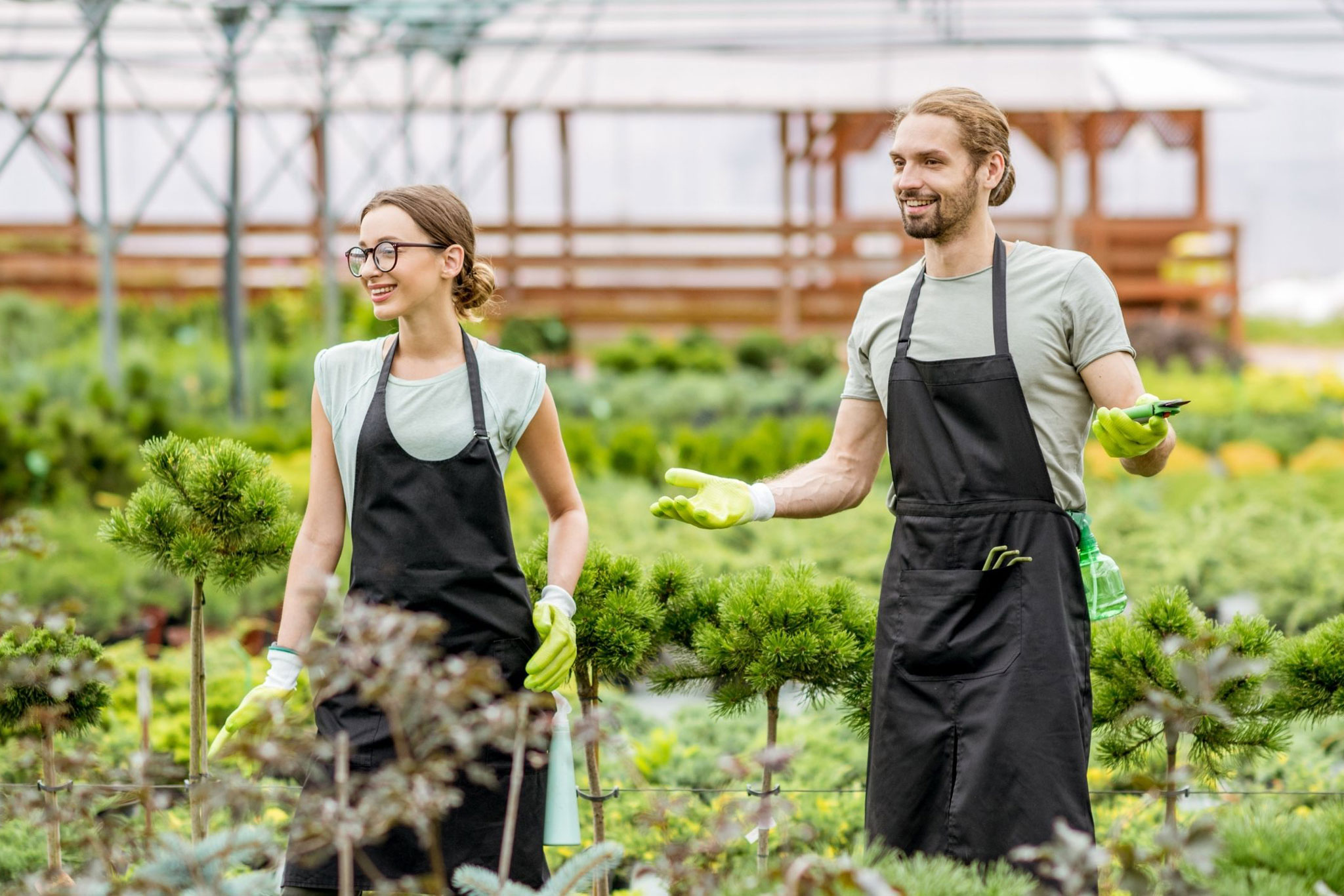 two young people working in a greenhouse surrounded by plants