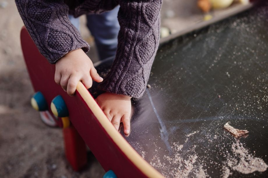close up on a toddler's hands playing at a sand table