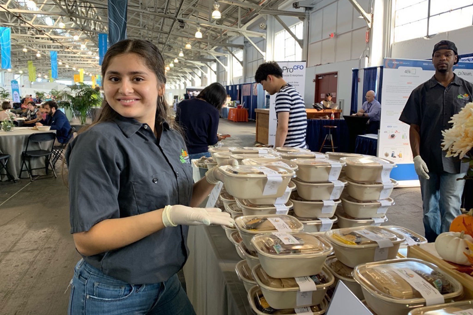 A worker from The Town Kitchen stands by a table of catered food at an event