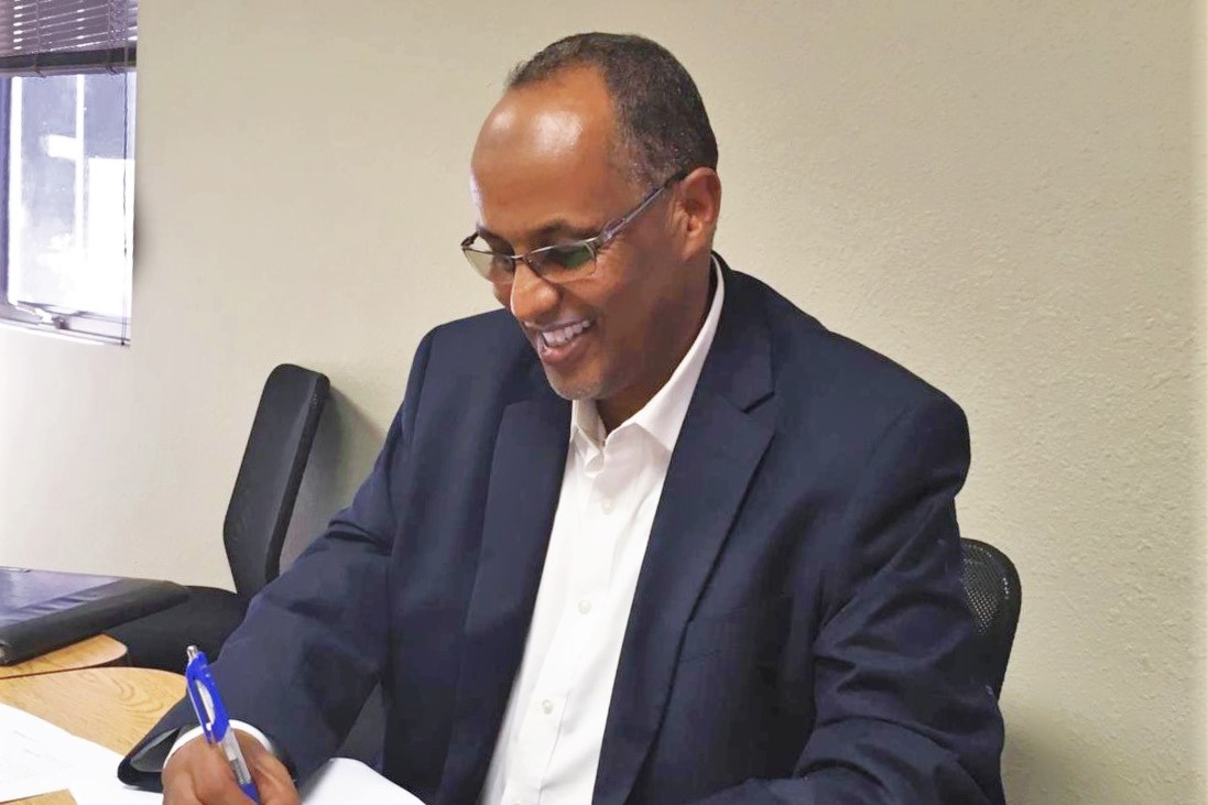 Ahmed Sahid of Somali Family Service of San Diego signing documents at MDF